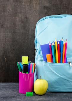 Вид спереди обратно в школу канцелярских товаров с красочными карандашами и яблоком
