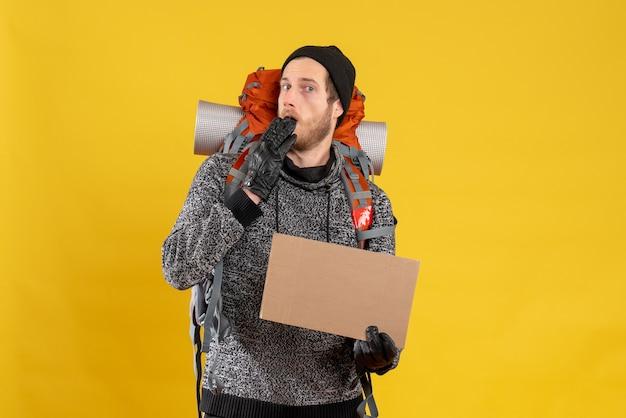 革の手袋と空白の段ボールを保持しているバックパックと困惑した男性のヒッチハイカーの正面図