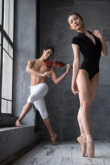 Вид спереди балерины в купальнике и мужской музыкант