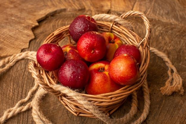 木製の机の上の桃と梅のバスケットの正面図