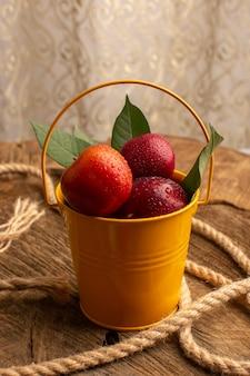 木製の机の上のロープと一緒にプラム新鮮でまろやかな果物が付いているバスケットの正面図