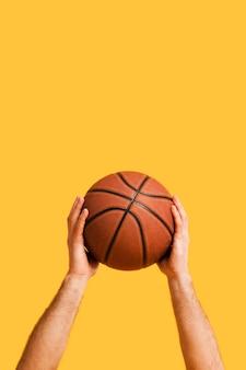 Вид спереди баскетбола, удерживаемого игроком мужского пола