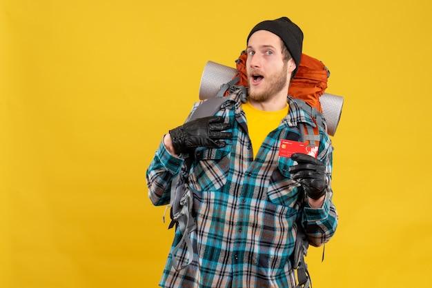 Вид спереди бородатого молодого человека с рюкзаком и шляпой, держащего кредитную карту