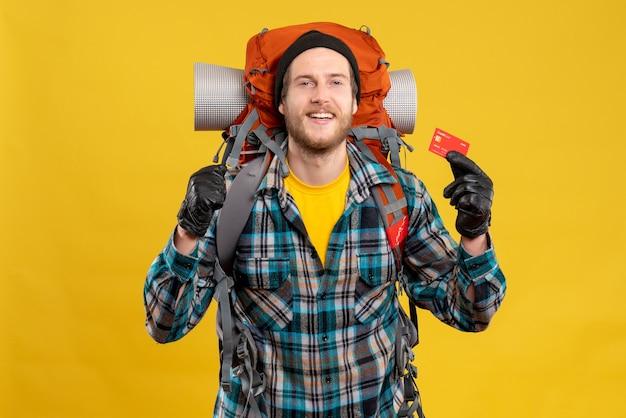Вид спереди бородатого молодого человека с рюкзаком, держащим кредитную карту