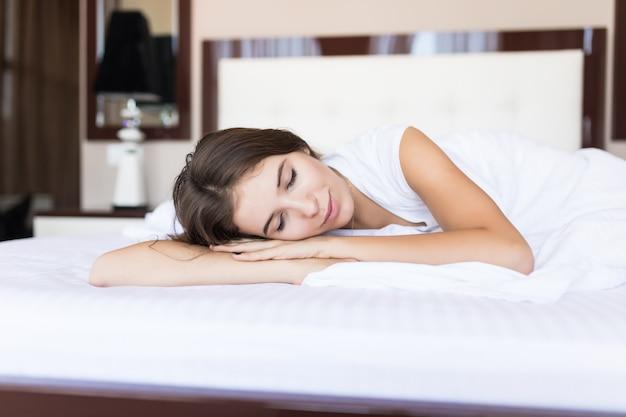 寝室の白い毛布の下で横になっている美しいブルネットの少女の正面図。カメラ目線と笑顔の魅力的な女性
