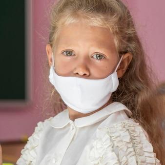 フェイスマスクを持つ美しい女の子の正面図