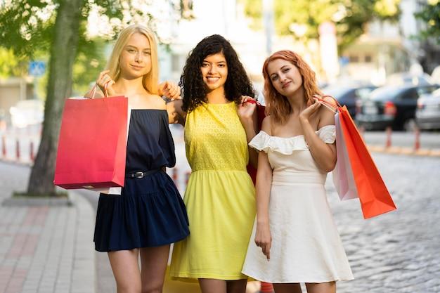 Вид спереди красивых девушек с хозяйственной сумкой