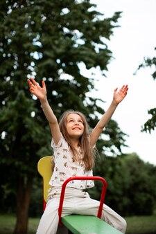 公園で美しい幸せな女の子の正面図