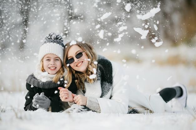 雪の上に横たわっている美しい母親と彼女の小さな愛らしい娘の正面図