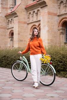 야외에서 자전거와 함께 포즈를 취하는 아름 다운 여자의 전면보기