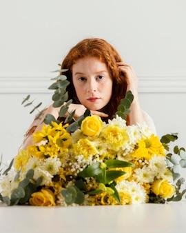 봄 꽃의 부케와 함께 포즈를 취하는 아름 다운 여자의 전면보기