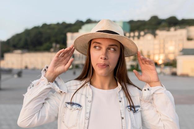 一人で旅行しながら帽子でポーズ美しい女性の正面図