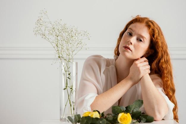 테이블에 봄 꽃과 꽃병과 함께 포즈를 취하는 아름 다운 여자의 전면보기
