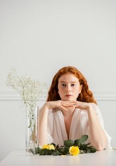 봄 꽃과 꽃병으로 포즈를 취하는 아름 다운 여자의 전면보기