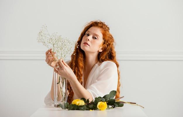 テーブルの上の春の花でポーズをとって美しい女性の正面図