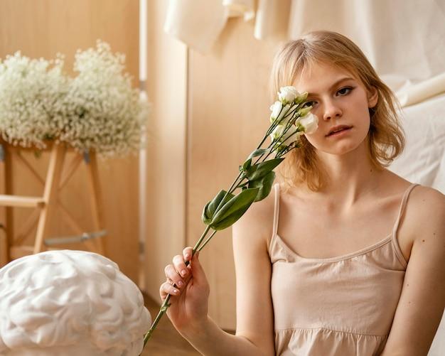 봄 꽃과 함께 포즈를 취하는 아름 다운 여자의 전면보기 프리미엄 사진