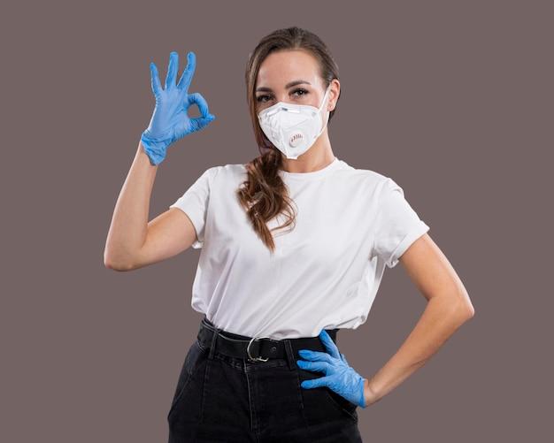 フェイスマスクを持つ美しい女性の正面図