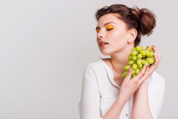Вид спереди красивой женщины с виноградом