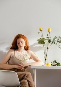 테이블에 꽃병에 봄 꽃과 함께 아름 다운 여자의 전면보기