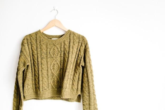 흰색 배경 근처 옷걸이에 아름다움 유행 녹색 여성 스웨터의 전면보기. 패션 컨셉.