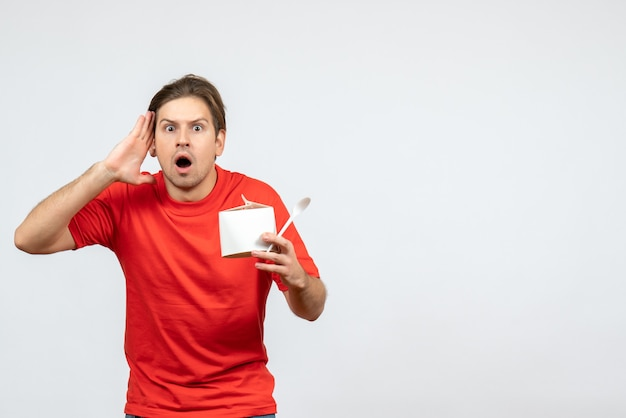 白い背景の上の紙箱とスプーンを保持している赤いブラウスで当惑した若い男の正面図