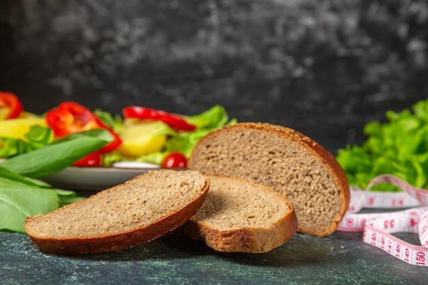 Вид спереди ломтиков черного хлеба, свежих нарезанных овощей на тарелке и метров зеленой пачки на поверхности темных цветов