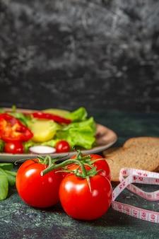 黒パンの正面図は、暗い色の表面に茎とメートルの緑の束で新鮮なトマトをスライスします