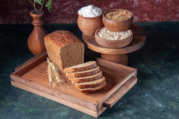 青い色の苦しめられた背景に茶色の木製トレイ小麦粉そばオートミールの黒いパンのスライスの正面図