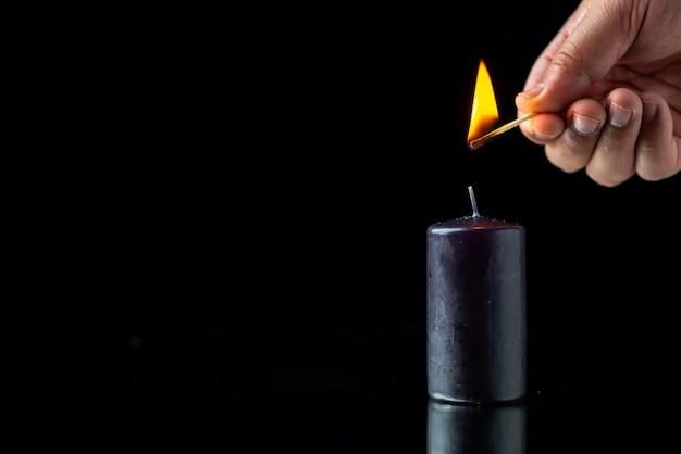 暗い表面で男性によって明るくなる黒いろうそくの正面図