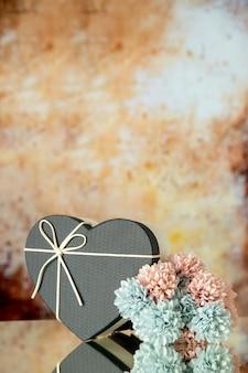베이지색 흐릿한 배경에 검정 하트 상자 색 꽃의 전면 보기