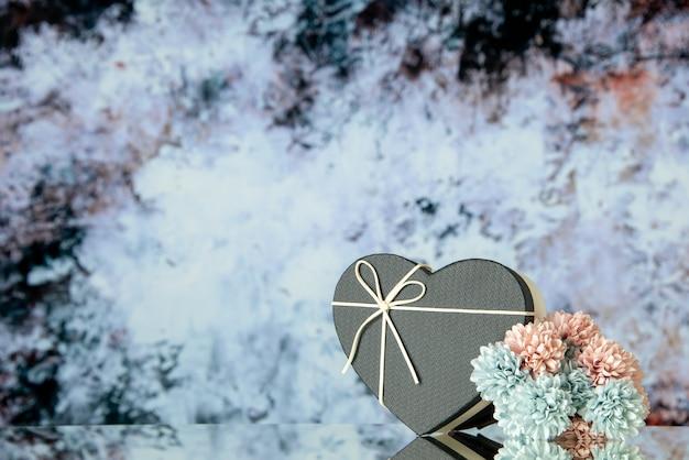 어두운 회색 추상적 인 배경에 검은 심장 상자 색 꽃의 전면 보기