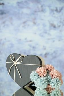 회색 추상적 인 배경에 검은 심장 상자 색 꽃의 전면 보기