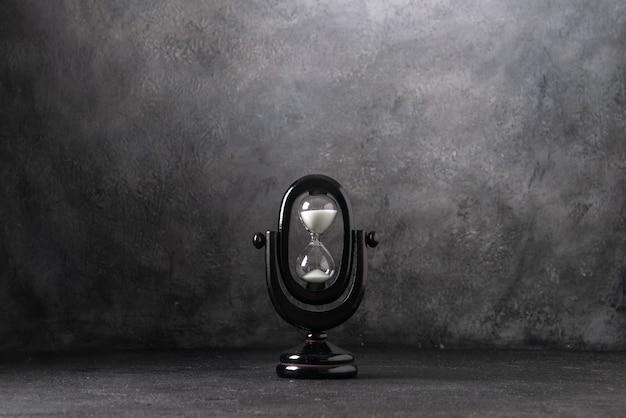 Вид спереди черные песочные часы на белой войне времени жизни