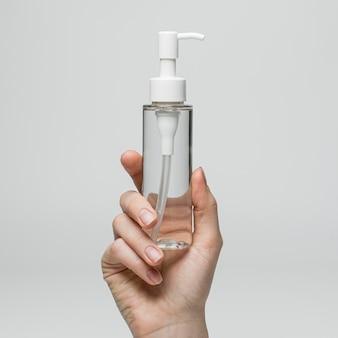 Вид спереди пустой упаковки косметического продукта в руке