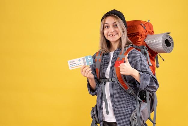 Вид спереди блаженной женщины-путешественницы с рюкзаком, держащей билет, показывает палец вверх