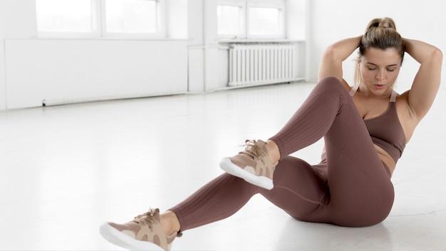Вид спереди блондинке, делая упражнения