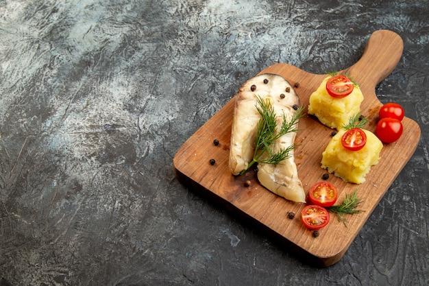 氷の表面に木製のまな板にトマト グリーン チーズを添えた魚のゆでそば粉の正面図