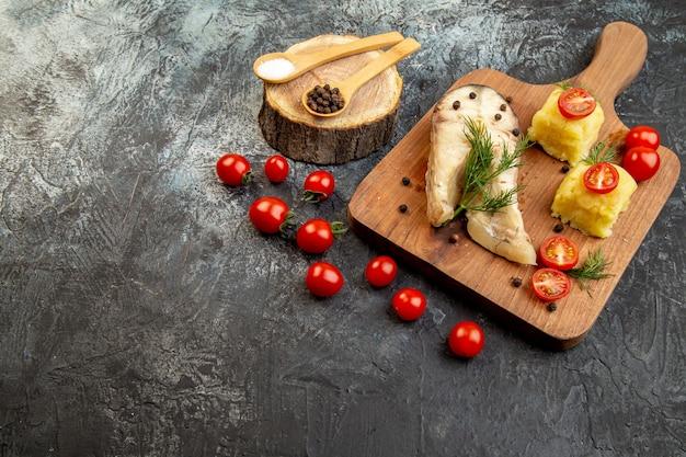 氷の表面に木製のまな板のスパイスにトマトのグリーン チーズを添えた、ゆで魚のそば粉の正面図