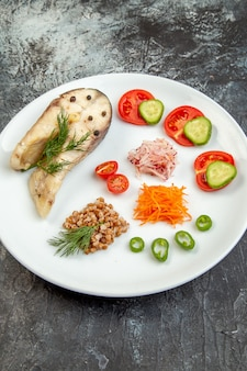 フリースペースのある氷の表面に白い皿に緑の野菜を添えた煮魚そばの正面図