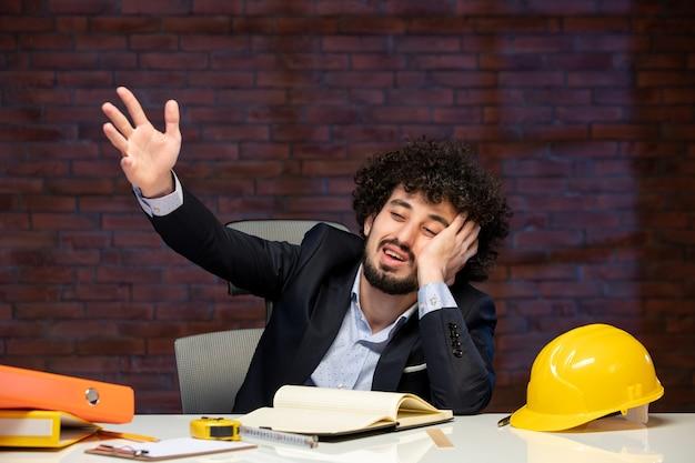 Вид спереди скучающего мужчины-инженера, сидящего за рабочим местом в костюме подрядчика, план работы строителя в помещении, корпоративный бизнес-проект