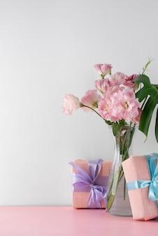 Вид спереди букет цветов в вазе с подарочными коробками