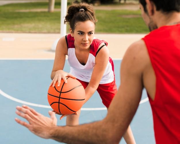 Вид спереди мальчика и девочки играют в баскетбол