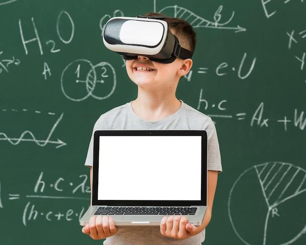 Вид спереди мальчика, держащего ноутбук во время ношения гарнитуры виртуальной реальности