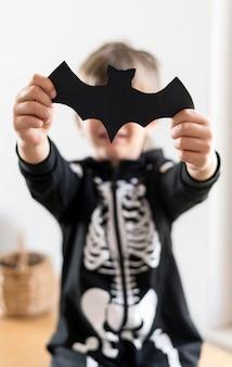 Вид спереди мальчика в костюме скелета