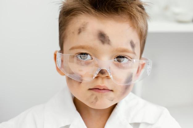 安全メガネと失敗した実験を持った実験室の少年科学者の正面図
