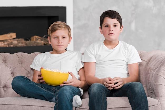 Вид спереди мальчиков, сидящих на диване