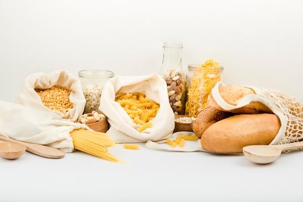 Вид спереди на хлеб в многоразовой сумке с макаронами и орехами