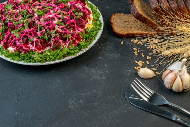 빵 조각 스파이크 칼 붙이 세트 마늘 칼 붙이 세트와 어두운 색 배경에 맛있는 샐러드의 전면 보기