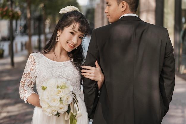 야외에서 그녀의 남편의 손을 잡고 신부의 전면보기