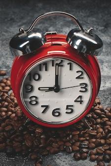 Вид спереди коричневых семян кофе с часами на темной стене